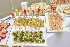 承办酒席开胃菜、快餐和点心食物桌  免版税库存照片