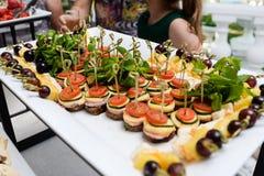 承办酒席服务板材 在塑料的开胃三明治在桌黏附rangeSandwiches自助餐 库存照片