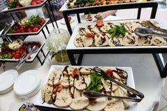 承办酒席服务板材 在塑料的开胃三明治在桌黏附rangeSandwiches自助餐 免版税库存图片