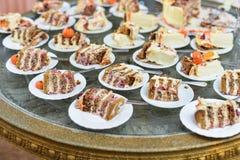 承办酒席服务板材 在塑料的开胃三明治黏附rangeSandwiches 免版税库存照片