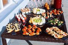 承办酒席用不同的食物快餐和开胃菜的宴会桌 免版税库存图片