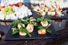 承办酒席用不同的食物快餐和开胃菜的宴会桌 库存图片