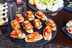 承办酒席用不同的食物快餐和开胃菜的宴会桌 图库摄影