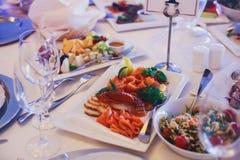 承办酒席用不同的食物快餐和开胃菜的宴会桌在公司圣诞节生日聚会事件 免版税图库摄影
