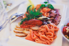 承办酒席用不同的食物快餐和开胃菜的宴会桌在公司圣诞节生日聚会事件 免版税库存图片