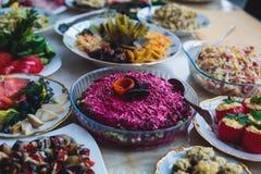 承办酒席用不同的食物快餐和开胃菜的宴会桌在公司圣诞节生日聚会事件 图库摄影