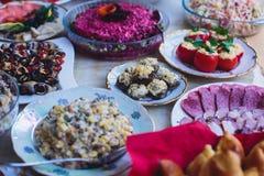 承办酒席用不同的食物快餐和开胃菜的宴会桌在公司圣诞节生日聚会事件 免版税库存照片