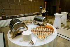 承办宴席-与各种各样的快餐的服务的桌 免版税库存图片