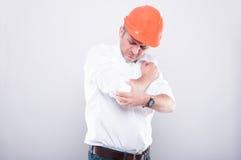 承包商佩带的安全帽画象拿着手肘的喜欢hurtin 免版税库存图片