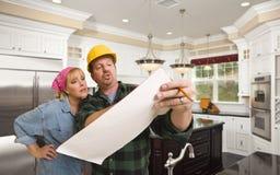 承包商谈论计划与在习惯厨房Int里面的妇女 库存照片