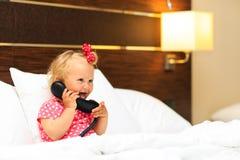 承担电话的逗人喜爱的小女孩在旅馆客房 免版税图库摄影
