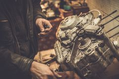 技工与与摩托车引擎一起使用 免版税库存照片