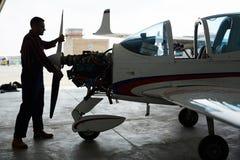 技工与飞机一起使用在飞机棚 免版税库存图片