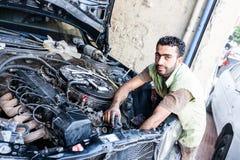 技工修理一辆老汽车的引擎 免版税库存图片