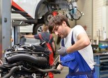 技工修理从一辆汽车的引擎在车库 库存图片