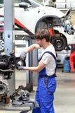 技工修理从一辆汽车的引擎在车库 库存照片