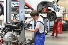 技工修理从一辆汽车的引擎在车库 免版税库存照片