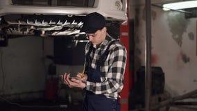 技工在汽车修理使用写下的剪贴板和的纸的服务中心完成的汽车维护的有些结果 股票视频