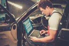 年轻技工在汽车车间 免版税图库摄影
