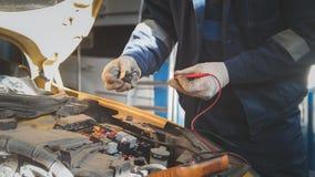 技工在自动车间与汽车电学-电子接线,电压表一起使用 图库摄影