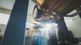 技工在车库机械车间检查汽车的底部-在汽车服务的被举的自动身分 库存图片