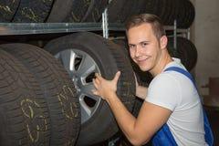 技工在车库的轮子或轮胎仓库 库存照片