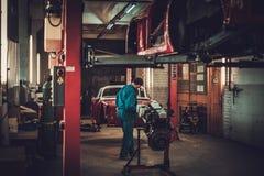 技工在经典汽车恢复车间 免版税库存图片