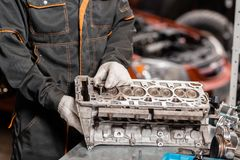 技工安装一个新的阀门 拆卸发动机组车 马达资本修理 十六阀门和四 免版税库存照片