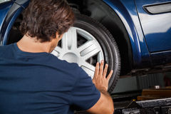 技工对车胎的定象轮毂罩 库存照片