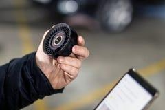 技工手拿着汽车备件和定购新的通过智能手机 车维护和服务statio 库存照片