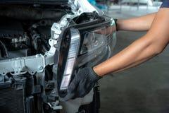 技工改变的汽车车灯在车间 免版税图库摄影