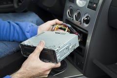 技工放汽车音频入汽车收音机口袋 连接收音机 库存照片