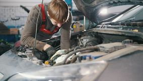 技工检查和修理汽车引擎,汽车修理,运作在车间,检修,在敞篷下 股票录像