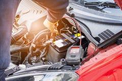 技工检查汽车电池电压电平的用途电压表 免版税库存照片