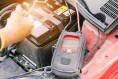 技工检查汽车电池电压电平的用途电压表 图库摄影