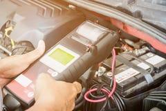 技工检查汽车电池的电压在汽车se的用途电压表 库存照片
