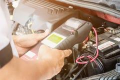 技工检查汽车电池的电压用途电压表 库存图片
