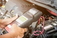 技工检查汽车电池的电压用途电压表 库存照片