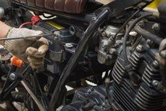 技工检查的手和增加制动液到摩托车, selec 免版税库存照片