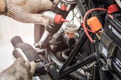 技工检查的手和增加制动液到摩托车, selec 图库摄影