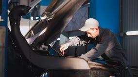 技工男性松开与在汽车的敞篷的一把螺丝刀SUV的 库存图片