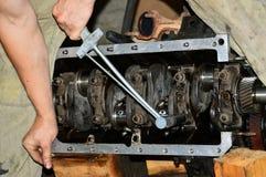 技工的手舒展内燃机的盖帽主要轴承有转矩扳手的 免版税库存照片