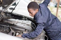 技工看一辆汽车的引擎在她的车间 免版税库存图片