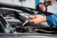 技工递填装的油入Car& x27; 在车库的s引擎 免版税库存照片