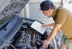 技工,拿着剪贴板的技术员人和检查汽车英国人 免版税库存图片