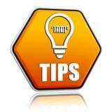 技巧和在橙色六角形横幅的电灯泡符号 库存照片