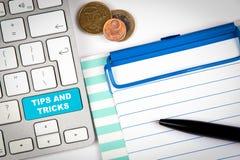 技巧和窍门 在白色办公桌上的键盘有各种各样的项目的 库存图片