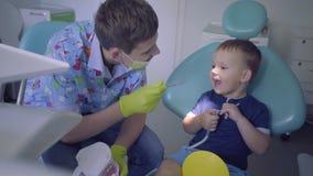 技巧男孩医疗使用在牙医办公室的面具和手套和小孩 教孩子的年轻人刷牙 影视素材