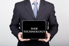 技术、互联网和网络在企业概念-拿着一台片剂个人计算机有网技术标志的商人 免版税库存图片