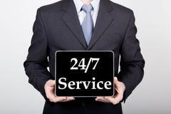 技术、互联网和网络在企业概念-拿着一台片剂个人计算机有24 7的商人为标志服务 库存图片